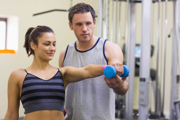 Instructor assisting content woman lifting dumbbells
