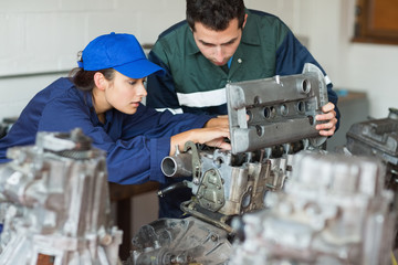 Focused trainee repairing engine with instructor