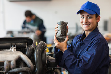 Happy trainee showing part of a machine