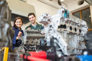 Smiling trainee and instructor repairing an engine