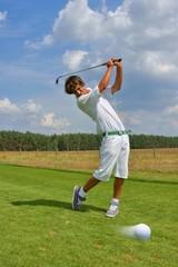 Golf, golfer striking the ball