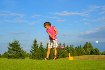 Golf, girl golfer hitting the ball