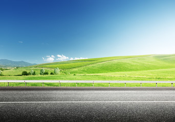 asphalt road and perfect green field