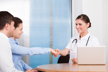Female Doctor And Woman Shaking Hands