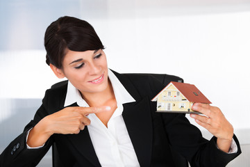 Young Businesswoman Pointing Towards House Model