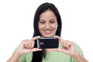 Young woman taking picture herself against white