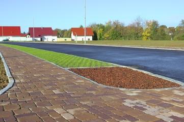 Neues Betonpflaster auf Parkstreifen und Gehweg mit Bauminsel