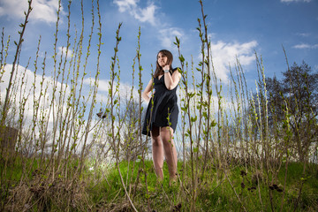 Young woman in black dress standing on glade near forest