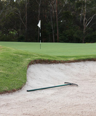 Rake in sand bunker at golf course