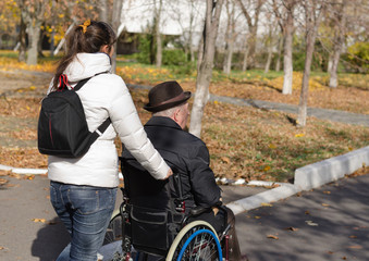 Woman pushing an elderly man in a wheelchair