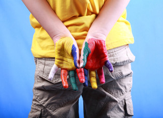 Kid in a yellow t-shirt showing painted hands on blue background