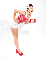 Sexy retro pin-up girl with radio and red lipstick wearing red s
