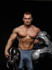 Man holding american football player accessories
