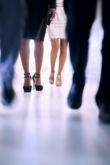 Low view of people walking down the corridor in an office building, focus on high heels