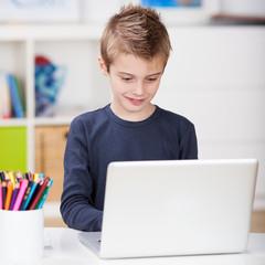 kleiner junge mit laptop im kinderzimmer