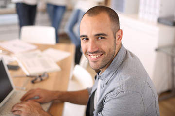 Smiling young man in office working on laptop