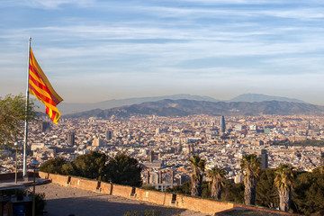 Aerial view of Barcelona city with flag of Spain