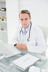 Serious male doctor with laptop at medical office