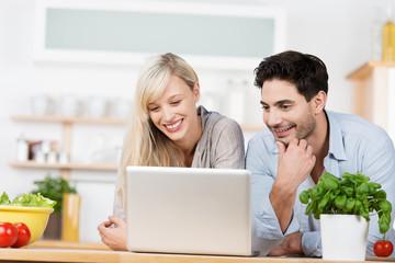 paar in der küche schaut lachend auf laptop