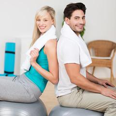 lachendes paar sitzt auf gymnastikbällen