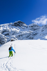 Skiing, Freeride  - Man with skis climbs to the top