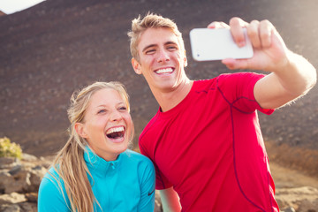 Young attractive athletic couple taking photo of themselves with