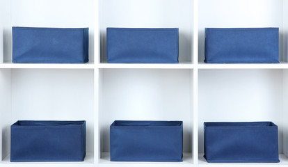 Blue textile boxes in white shelves