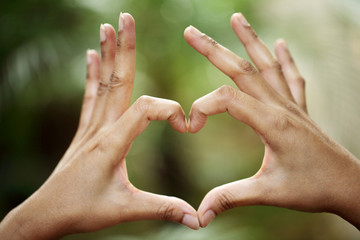 hands in the form of heart shape against green