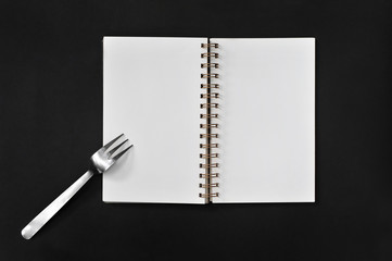 Blank notepad with fork on black - concept : planning and eating