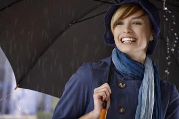 Young woman using umbrella in rain