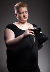 Chubby woman taking pictures of old camera