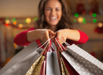 Closeup on christmas shopping bags in hand of smiling woman