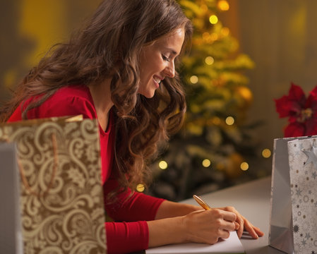Happy young woman making christmas list of presents