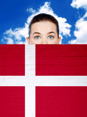 woman face behind wall with denmark flag
