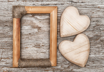 Wooden hearts and frame on the old wood