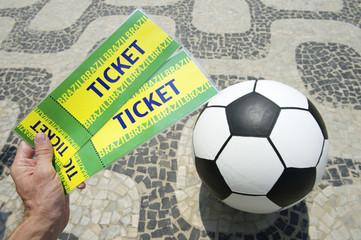 Soccer fan holds tickets above football in Brazil