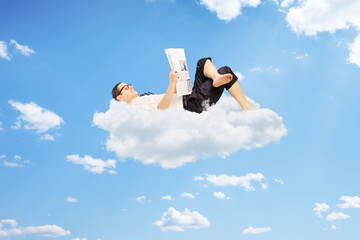 Young male reading newspaper and lying on clouds