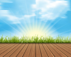 Wood floor with green grass isolated on blue sky and sunlight