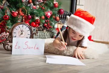 Pretty little girl in Santa hat writes letter to Santa