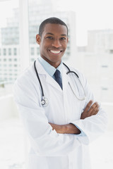 Smiling doctor with arms crossed in a medical office
