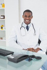 Smiling male doctor sitting with computer at medical office