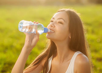 Portrait half face of young woman drink water bottle at summer