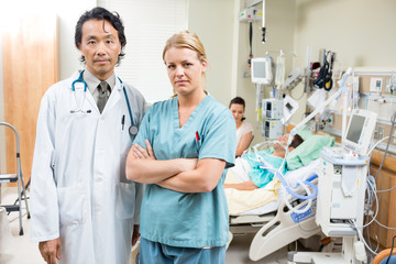 Confident Doctor And Nurse With Patient Resting In Hospital