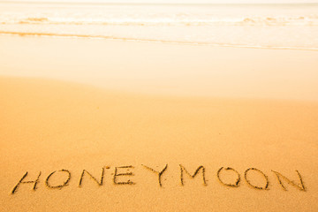 Honeymoon, text written in sand on a beach, with a soft wave.