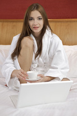 Portrait of beautiful woman with laptop on bed