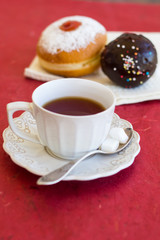 A cup of tea with fresh chocolate donuts