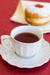 A cup of tea with fresh donut