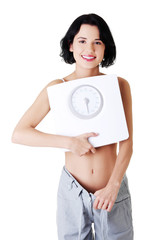 Attractive woman in baggy trousers with scale.