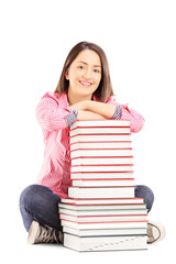 Smiling young female student sitting next to a pile of books