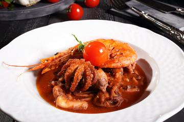 zuppa di pesce calamari e gamberi piatto bianco